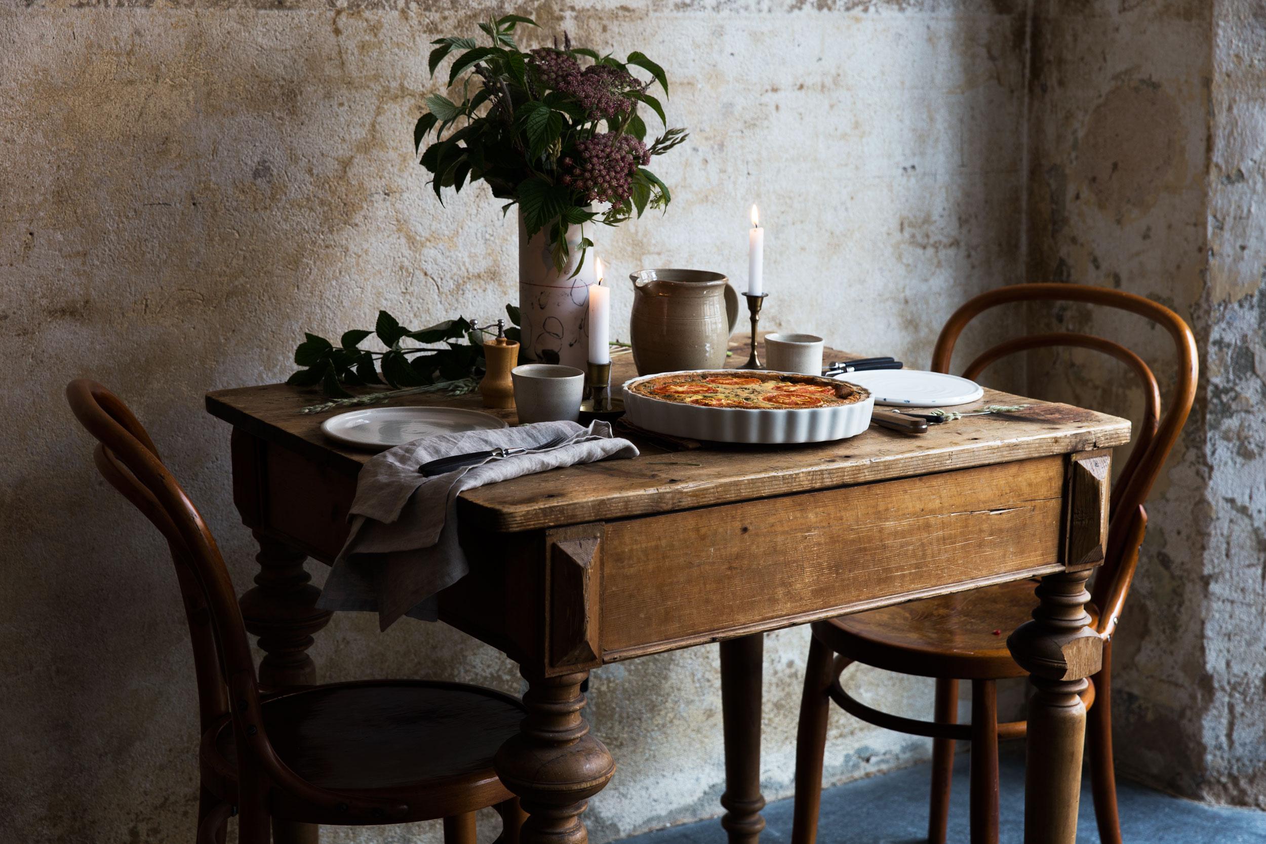 Rustikal gedeckter Tisch mit Tomaten-Quiche